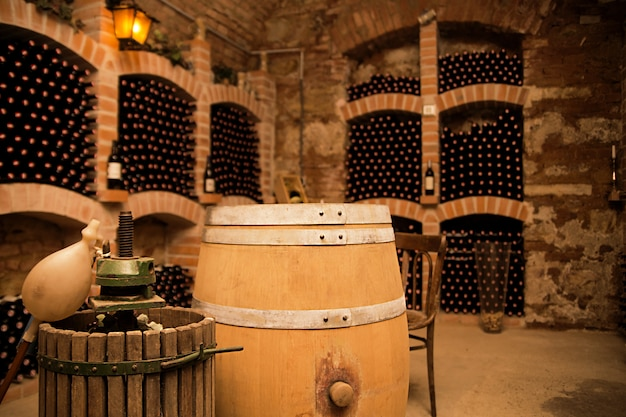Small and old wine cellar with many full bottles and keg Premium Photo