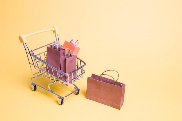 노란색 배경에 미니어처 쇼핑 트롤리에 작은 종이 봉지 프리미엄 사진