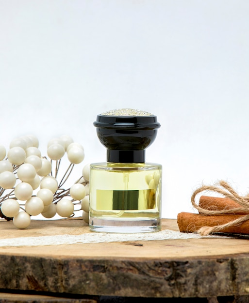 Small perfume bottle with black lid decorated with cinnamon stick Free Photo