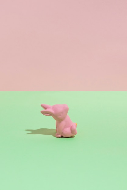 Small pink toy rabbit on green table Free Photo