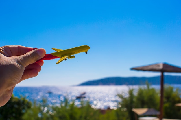 Small plane in female hand on background of blue sky Premium Photo