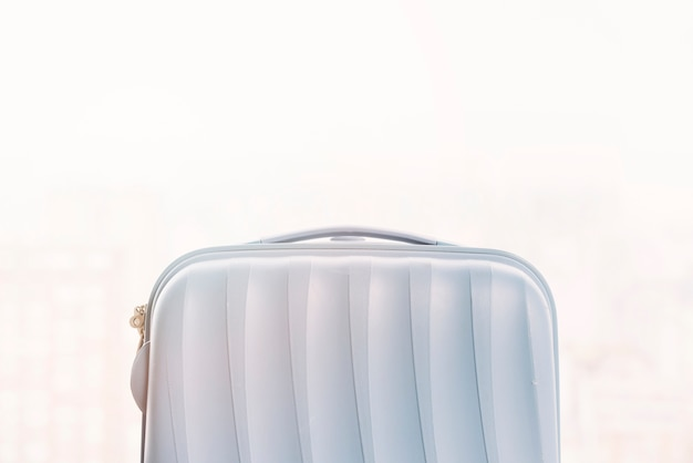 Small plastic luggage bag against white background Free Photo
