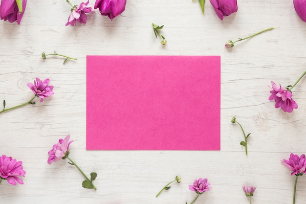 Small purple flowers with paper on table Free Photo
