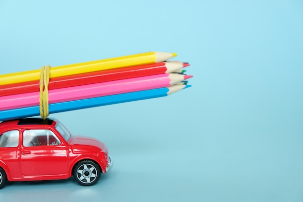 A small red car driven by colored pencils Premium Photo