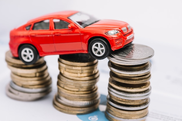 Small red car over the stack of increasing coins Free Photo