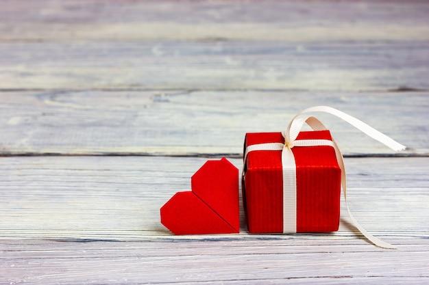 白いリボンとハートの形のメモで結ばれた小さな赤い贈り物 Premium写真