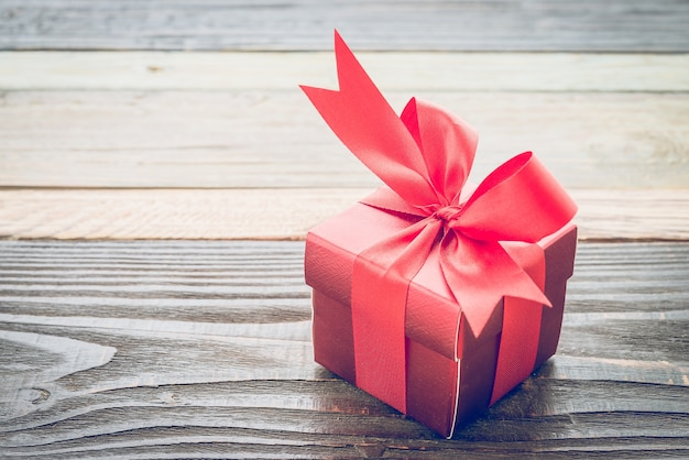 Small red gift on a wooden table Free Photo