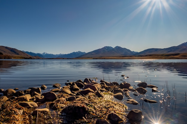 Small rocky promontory leading out to the calm lake with the southern alps Premium Photo