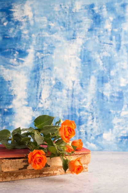 Small roses and old book on blue background Free Photo