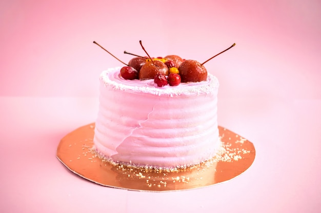 Small round pink birthday cake with mastic and decor fruits Premium Photo