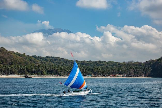 Небольшой парусник плывет по воде с прекрасным видом на горы. Бесплатные Фотографии