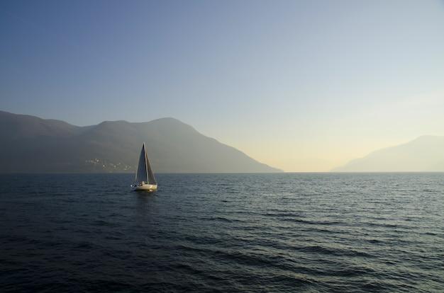 Маленькая парусная лодка в озере с закатом Бесплатные Фотографии
