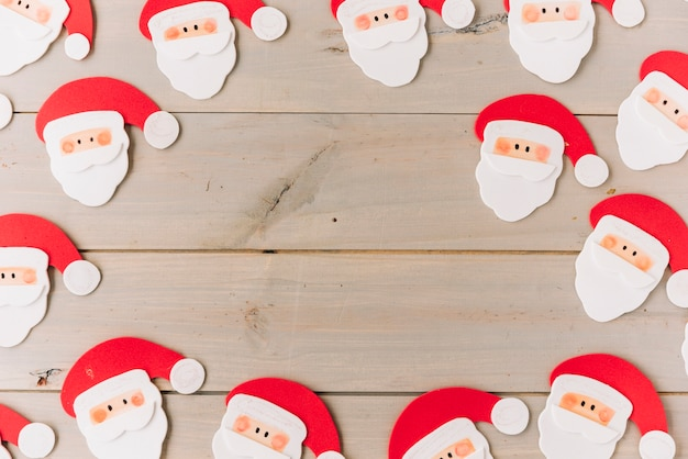 Small santa clauses on wooden table Free Photo