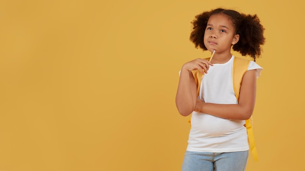 Small school girl copy space yellow background Free Photo