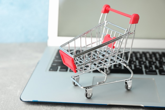 작은 쇼핑 카트 및 노트북 복사 공간 프리미엄 사진