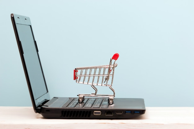 Small shopping cart on laptop for shopping online. technology business online concept. Premium Photo
