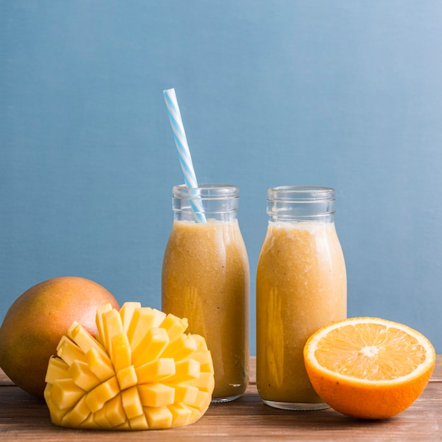 Small smoothie bottles with mango and orange Premium Photo