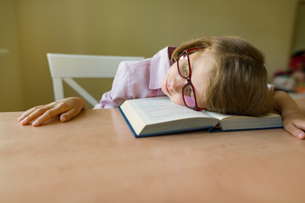 Small student in glasses sleeps at a desk Premium Photo