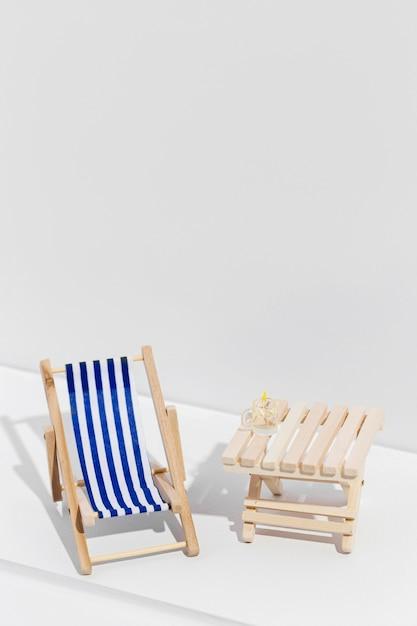 木製のテーブルの横にある小さなサンベッド 無料写真