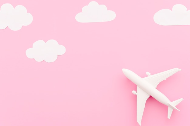 Small toy plane with paper clouds Free Photo