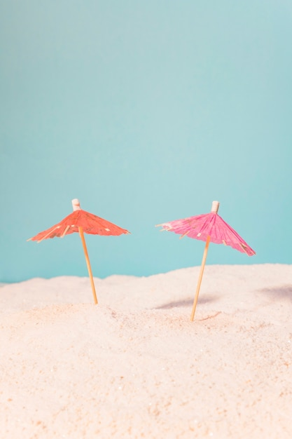 Small umbrellas for drinks in sand Free Photo