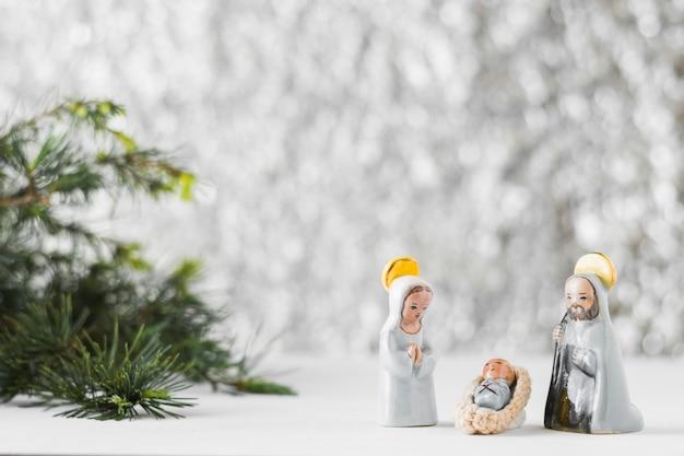 Small virgin mary with baby jesus and saint joseph near fir tree Free Photo