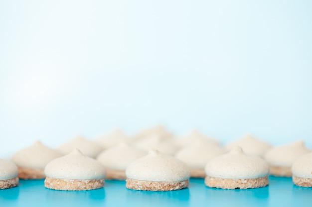 Small white cakes on a blue background Premium Photo