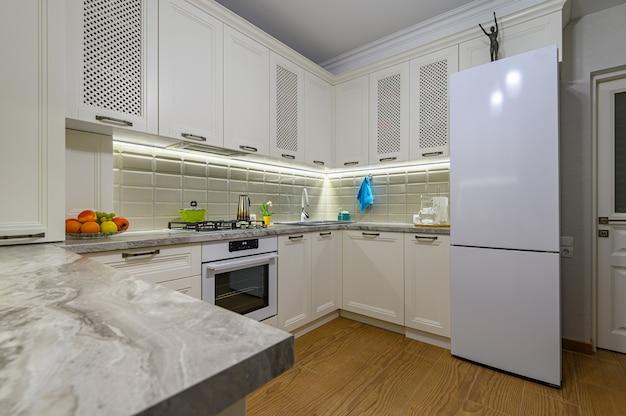 Маленькая белая уютная и удобная современная кухня в классическом стиле с деревянной мебелью Premium Фотографии