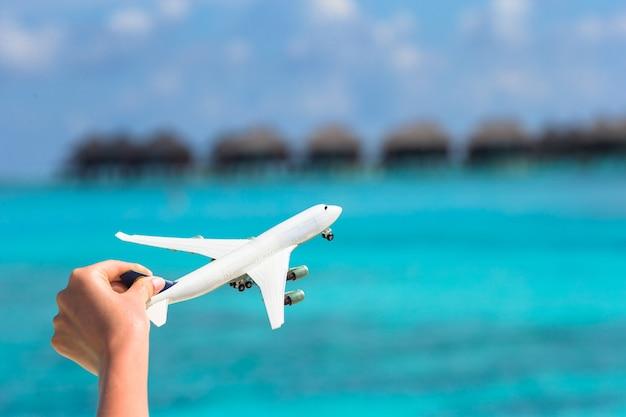 Small white toy airplane on tropical beach water bungalow Premium Photo