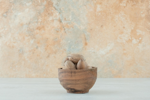 A small wooden bowl of nuts on white background. high quality photo Free Photo