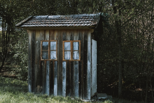Small wooden cabin with brown windows with white curtains in a forest surrounded by trees Free Photo
