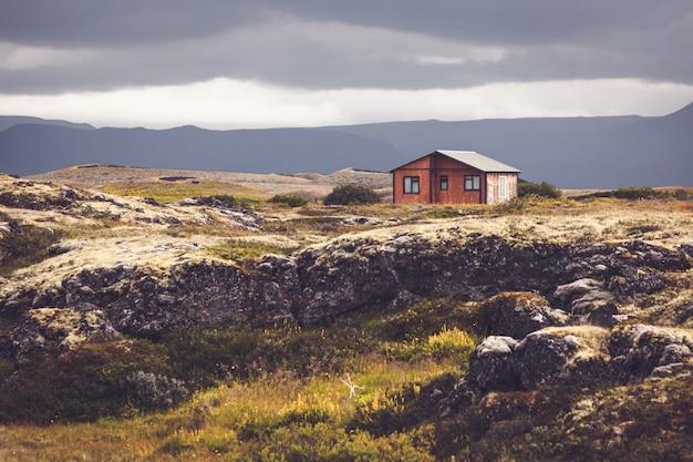 アイスランドの火山の風景の中の小さな木造コテージ Premium写真