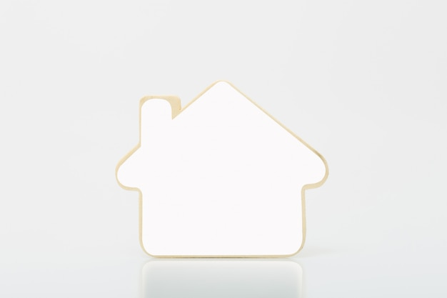 Small wooden home with white blank on tabel. concept for real estate busines. Premium Photo