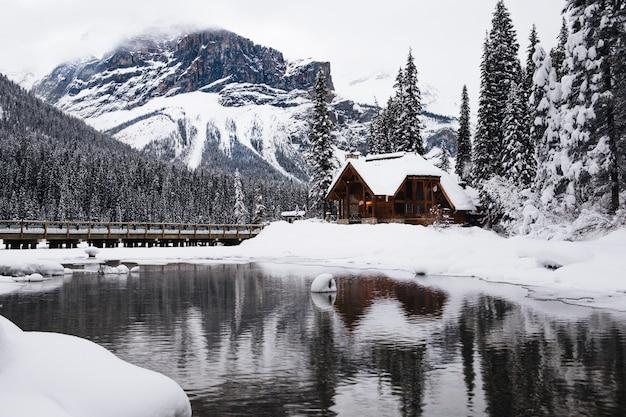Piccola casa di legno ricoperta di neve vicino al lago smeraldo in canada in inverno Foto Gratuite