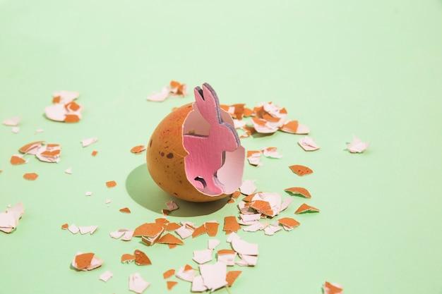 Small wooden rabbit in broken egg Free Photo