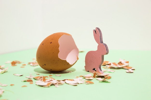 Small wooden rabbit with broken egg on table Free Photo