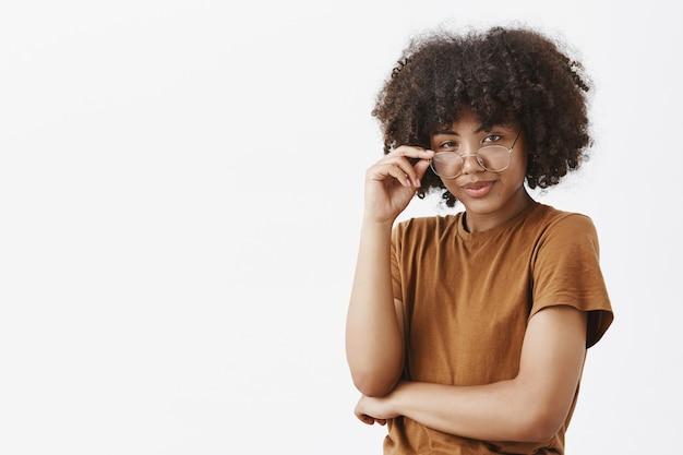 スマートなアフリカ系アメリカ人の女性の天才、アフロのヘアスタイルをトレンディな茶色のtシャツでメガネの下から見ている 無料写真