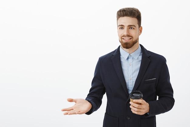 ビジネスパートナーと話している休憩中にコーヒーの紙コップを保持しているスタイリッシュなスーツでスマートで創造的なカリスマ的な男性起業家が仕事とお金を保証する笑顔で身振りで示すビジネスパートナーと話しています。 無料写真