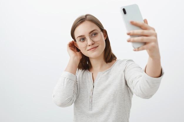 メガネのスマートで優しい女性が耳の後ろで髪束をフリックし、真新しい灰色の壁の上でポーズをとっている真新しいスマートフォンで自分撮りをしながらかわいい笑顔でソーシャルネットワークに投稿 無料写真