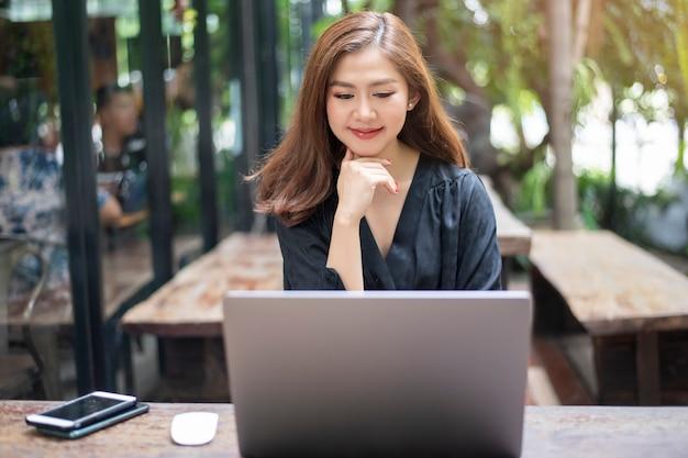 Умная азиатская женщина работает с ноутбуком Premium Фотографии