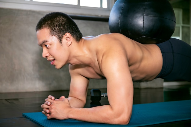 Smart asian man in sportswear training abdominal muscles with planking at fitness gym Premium Photo