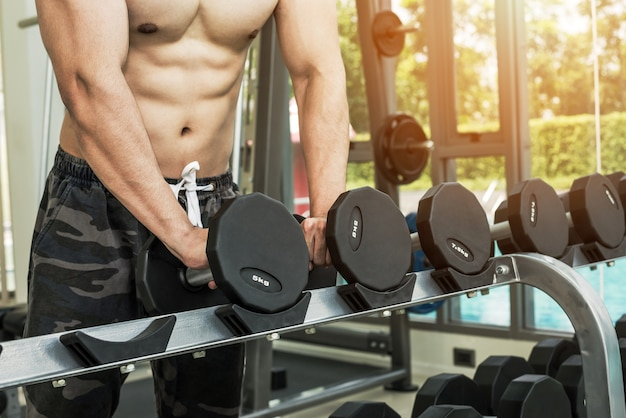 Smart athlete man selecting dumbbells for lifting and