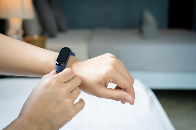Smart band, women touching fitness smart band on her hand Premium Photo