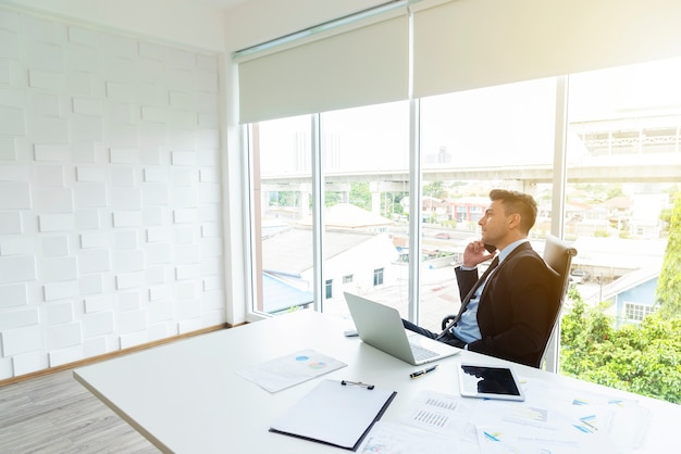 Smart businessman using mobile to contact to people in office Premium Photo