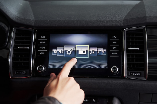 Smart car and internet of things iot concept. finger point to car 's console and icons popup out of screen Premium Photo