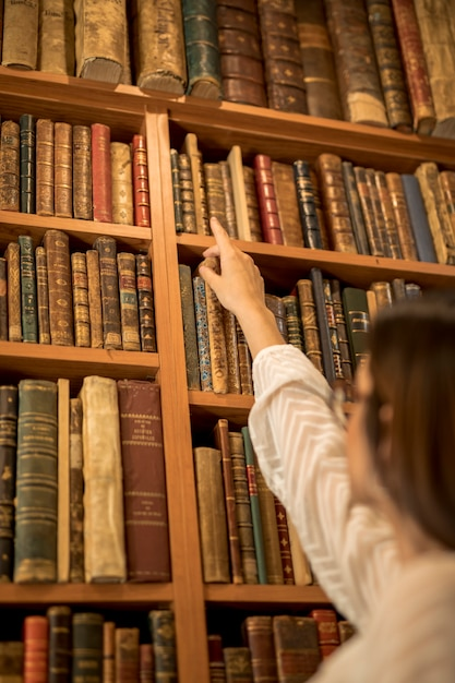 Smart female student looking for book in library Free Photo