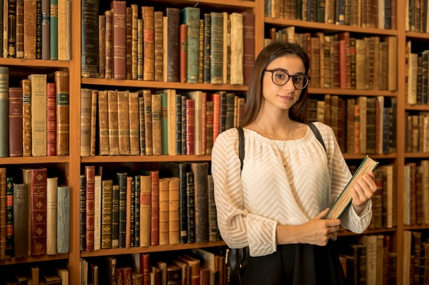 Smart female student with book in library Free Photo