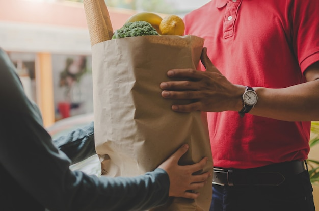 Smart food delivery service man in red uniform handing fresh food to recipient and young woman customer receiving order from courier at home Premium Photo