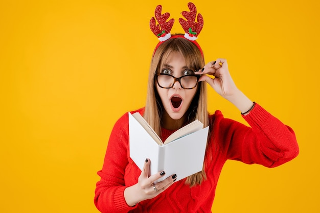 Smart funny girl holding book with copy space cover reading with glasses Premium Photo