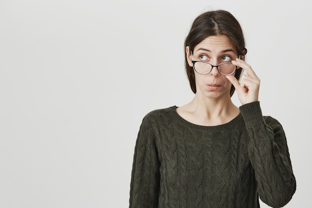 Smart girl in glasses looking upper left corner intrigued, peeking Free Photo
